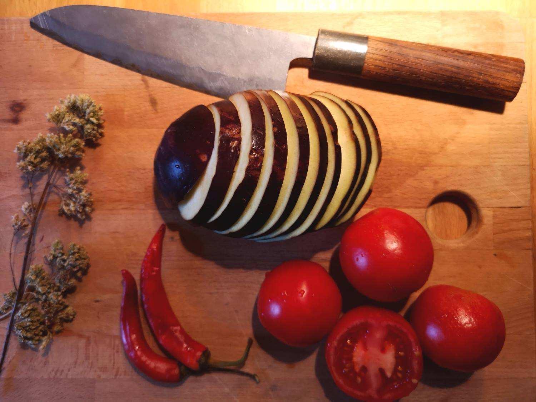 Aubergine und Tomate auf einem Holzbrett geschnitten